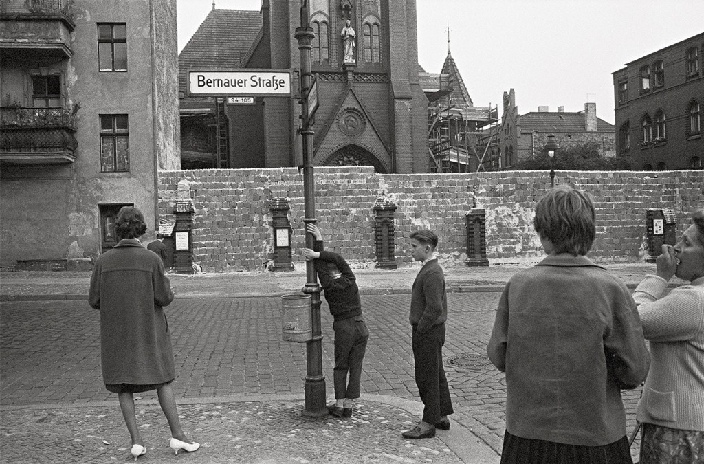 People in West Berlin look at an early version of the Berlin Wall